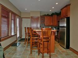 Fully equipped kitchen with cherry finished cabinetry and kitchen bar.