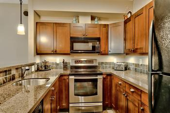 Kitchen with granite counter tops, microwave, dishwasher, toaster, coffee maker, flat cooktop and oven.