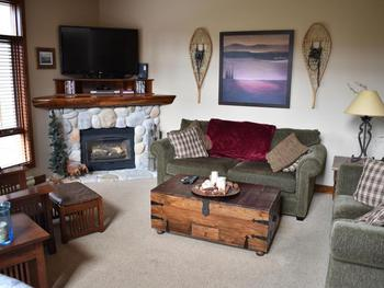 Living room with seating for six, gas fireplace and flat screen TV.