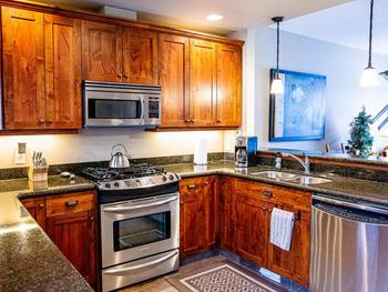 Gourmet kitchen with stainless steel appliances, granite countertops, and heated floors.