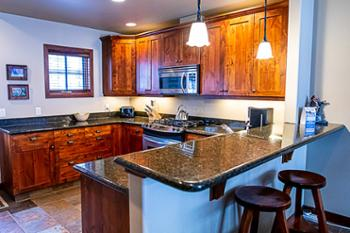 Kitchen has an elevated granite breakfast/eating bar with two stools for quick meals or snacks.