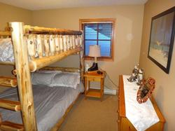 The third bedroom with a double over queen, rustic log bunk bed.