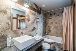 Main bathroom is located off of the dining room with access to the guest bedroom. This 4 piece bathroom boasts a soaker tub, hand held shower, concrete heated floors and plenty of storage.