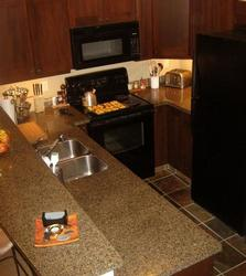 Fully equipped kitchen with heated tile floors, by the dining area with table for six.