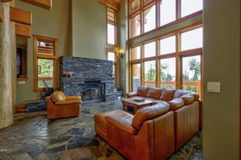 Great Room with large sectional, floor to ceiling windows, huge fireplace & deck
