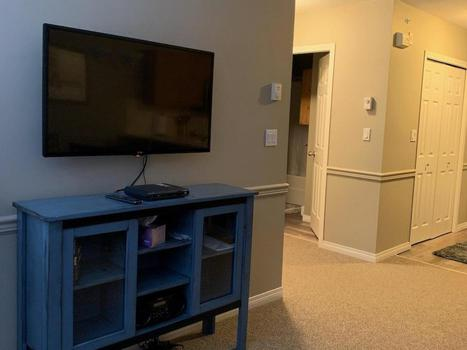 new tv and cabinet with books, games and puzzles