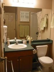 Bathroom with numerous amenities: Soap, hair dryer, Q-Tips, cotton balls, moisturizing lotion, magnifying mirror.