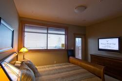 All Bedrooms are equipped with flat panel TVs. Here you can see the Guest Bedroom walks out to the deck and hot tub.