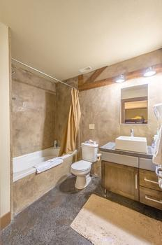Bunk room en-suite with shower and bathtub combination.