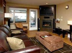 Cozy lounge with natural gas fireplace and large screen plasma TV above.