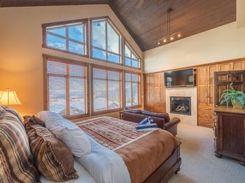 Tasteful Master bedroom with king bed, quality linens and bedding, fireplace with flat screen TV, leather sofa, ensuite with steam shower, and cathedral windows.