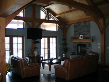 Great Room with fireplace and high vaulted ceilings. The large windows and doors let in lots of light and provide a great view of the three mountains.