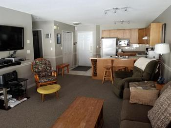 Living / Dining Area with double pull-out couch, flat screen TV, fire place and mountain view