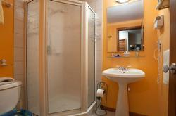 Newer shower stall in second bathroom with extra towel racks, towel shelf and hair dryer. Dual shower heads.