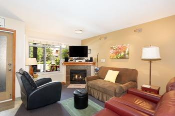 Spring view of living room, wall art has changed since this photo. Gas fireplace. View of front patio and pool area.