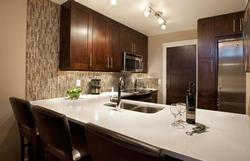 The kitchen features stylish cabinets, countertops, lighting and stainless appliances.