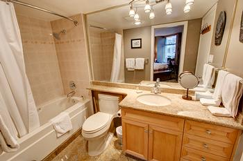 Full bathroom with granite counter-top & absolutely beautiful single-piece granite slab flooring.