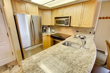 Fully equipped kitchen with granite counter-tops, granite back-splash and full-size stainless steel appliances.