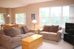 Bright and spacious living room features comfortable seating, a large flat screen TV, lazy boy recliner, cozy gas fireplace, a selection of music, board games and books.
