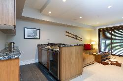 Media room wet bar: including a sink, under counter fridge and dishwasher and large flat screen TV