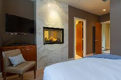Master bedroom with TV and see through fireplace into master ensuite