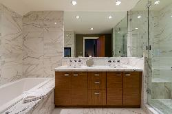 Master bathroom: see thu fireplace, deep soaker tub, hued wall to wall stone, double undernmount sinks, stone counters, heated flooring,