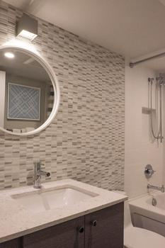 Brand new bathroom with tub, quartz counter top & tiled wall.