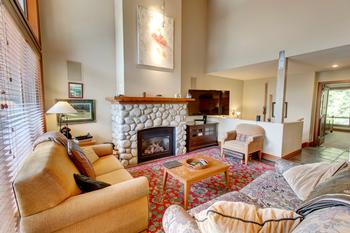 Great room has cathedral ceilings, with river rock fire place and a complete entertainment system