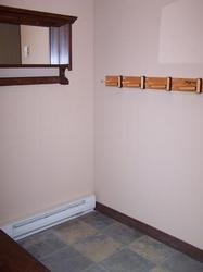 Ski and equipment storage at entry. Additional coat hooks on adjacent wall.