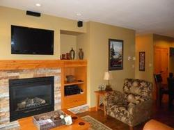 a cozy living space with fireplace, leather couch and flat screen TV and entertainment centre