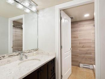 The modern and sleek bathroom has ample room for a family with a steam shower and many items included in the cabinets for convenience.