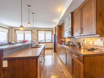 Fully appointed kitchen with gas range, side by side stainless fridge and dishwasher.