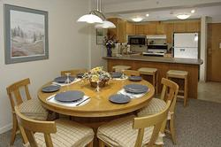 dining area with large round dining table and breakfast bar