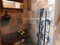 Tiled entry foyer with ski rack and heated boot pole storage