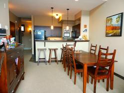 looking through the dining area to the kitchen, with kitchen bench and 3 bar stools from where you can support the chef
