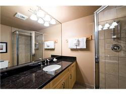 The on suite bathroom includes a rain shower head and heated tiled floors.