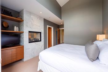 Master bedroom with king bed, TV and see through gas fireplace