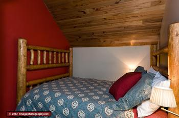 This is the second bedroom. This room is located beside the living room and contains a double bed. Although not visible in this picture, the wall on the fourth side does not extend to the ceiling. The bedroom is open at the ceiling level to the living room. There is sufficient headroom above the bed for 2 adults to be comfortable. This room contains an armoire for storage.