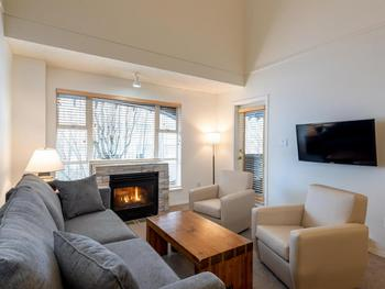 Spacious livingroom with fireplace, dining seating for 8, and private deck overlooking the Upper Village and base of the Mountain