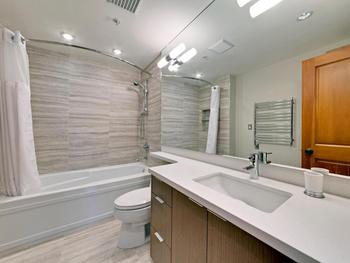 Ensuite master bathroom with tub and shower, heated floors, linen storage and heated towel rail.