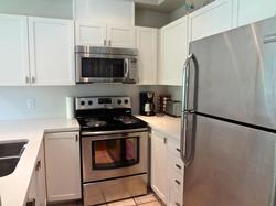 Fully updated kitchen with quartz countertops and all stainless steel appliances: fridge/freezer, stove, microwave/hoodfan and dishwasher