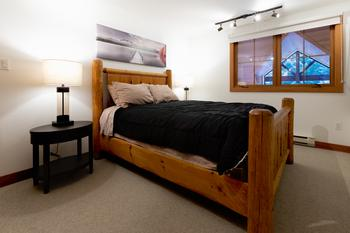 Generous size master bedroom features a custom made queen bed with views of living room below and trees facing Blackcomb Mountain's Wizard chair. Watch television or DVD from your bed. Closet is located to the left of the bed.