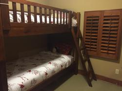 Bunk room downstairs with single over single bunk bed