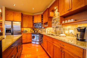 Open kitchen with stainless steel appliances and granite countertops.