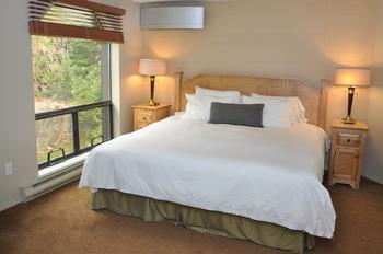 Large master bedroom with king size bed, ensuite and air conditioning / heating unit.