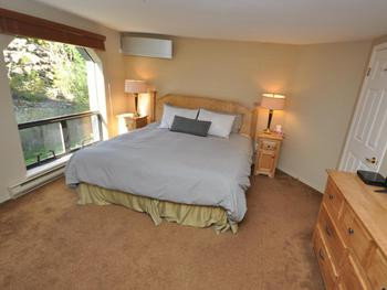 Large master bedroom with king size bed, ensuite with bathtub & shower, TV, and air conditioning.