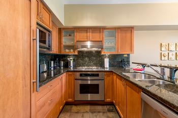 Heated tile flooring in the kitchen with high-end stainless-steel oven, gas stove, microwave and dishwasher and large capacity built in refrigerator with bottom drawer freezer.