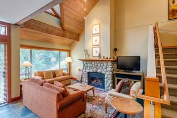 Vaulted ceiling living room with river rock fireplace and views to Whistler and Blackcomb slopes