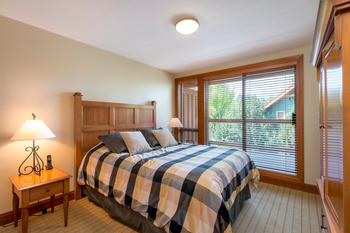 Queen-size bed in the third bedroom with sliding glass doors to the deck.