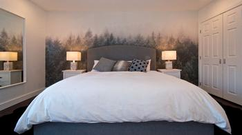 featured wallpaper, upholstered king bed, marble lamps, dual sheepskin rugs